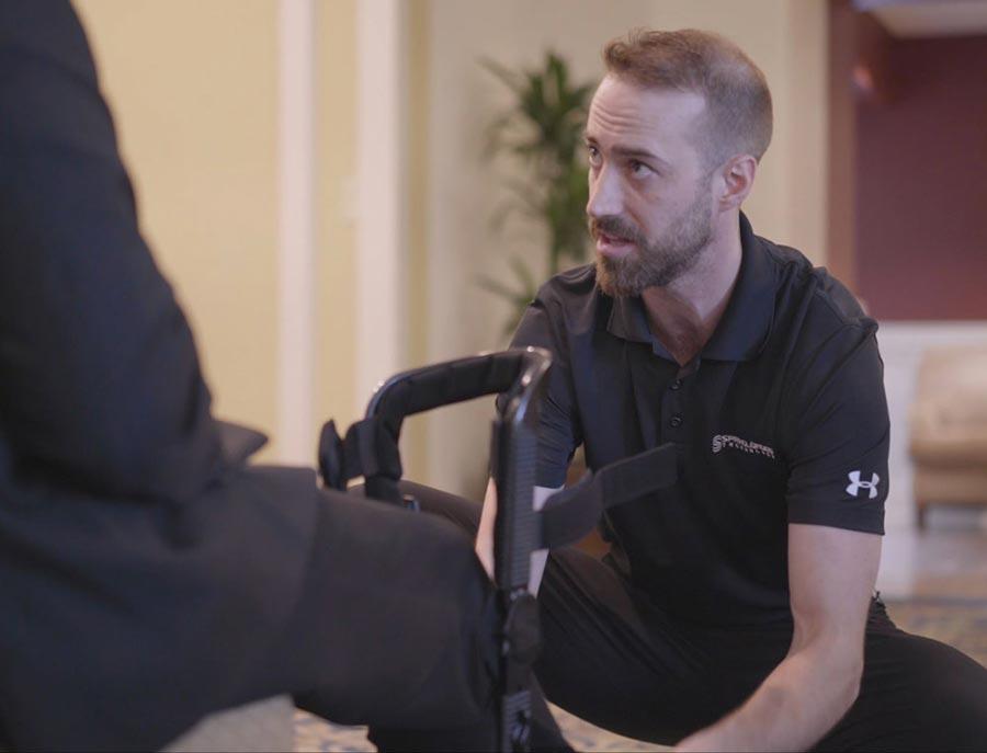 Man fitting knee brace on client